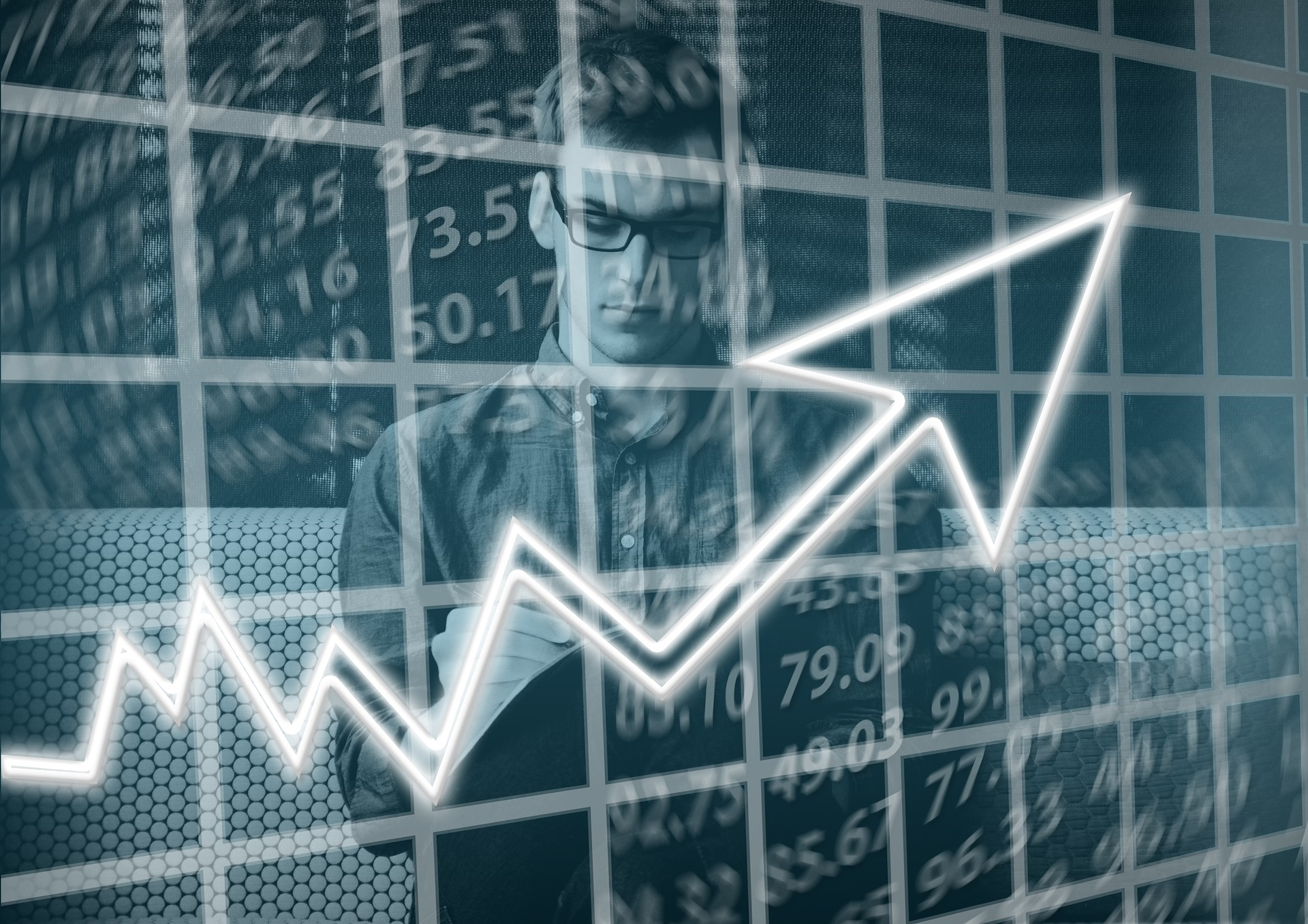 man behind image of graph with arrow pointing upward