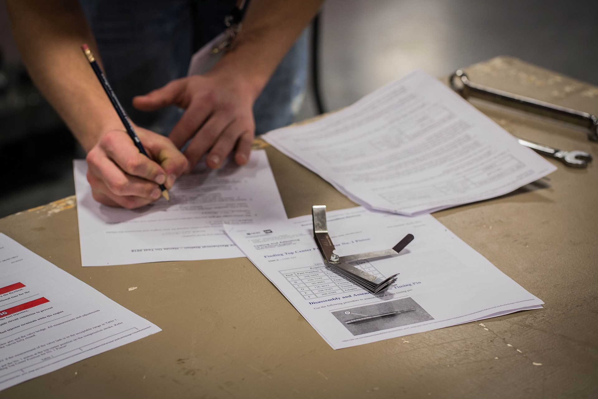 person writing on assessment papers on desk